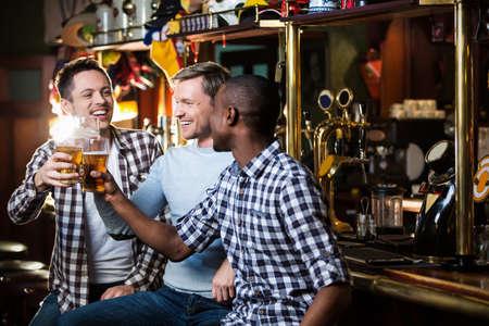 young guy: Happy men with beer in bar