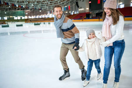 Smiling family at ice-skating rink Banque d'images