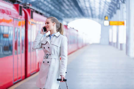 Smiling businesswoman with phone at station