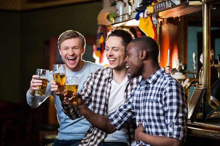 Uomini felici con la birra in un pub