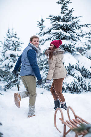 winter couple: Smiling couple with a sled Stock Photo