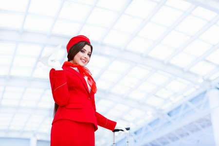 stewardess: Young stewardess with a plane at airport