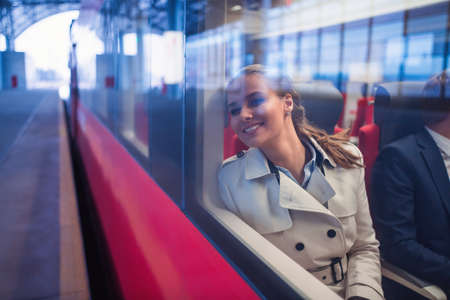 Donna sorridente in un treno Archivio Fotografico - 61584931