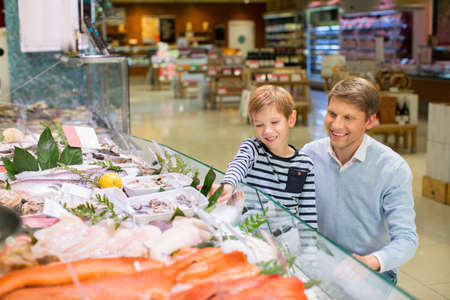 fish shop: Dad and son at showcase