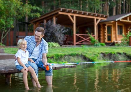S úsměvem otec a syn rybaření venku Reklamní fotografie