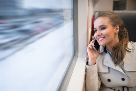 Smiling woman with mobile in train