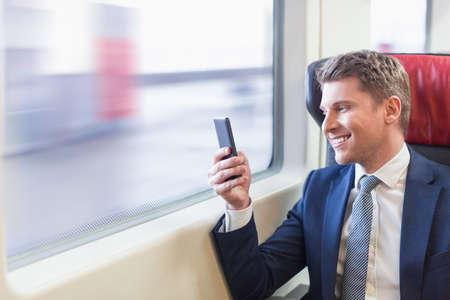 Uomo d'affari sorridente in un treno Archivio Fotografico - 64730169