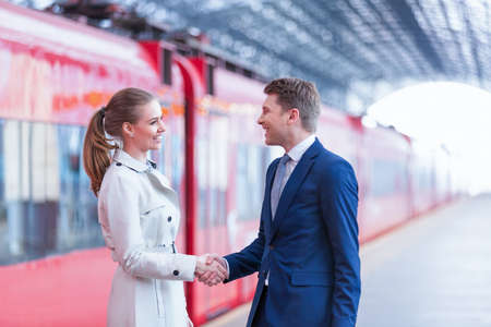 public transport: Smiling business people at station Stock Photo
