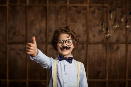 finger bow: Smiling boy with a bow indoors