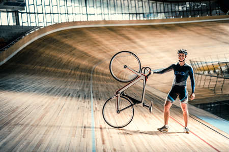 sports track: Athlete with a bicycle on a sports track Stock Photo