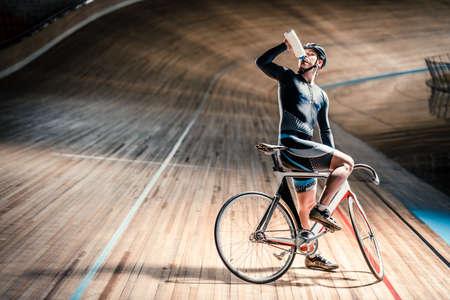 Drinking athlete on velodrome Foto de archivo