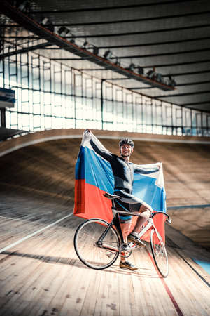 sports track: Bicyclist with flag on a sports track Stock Photo