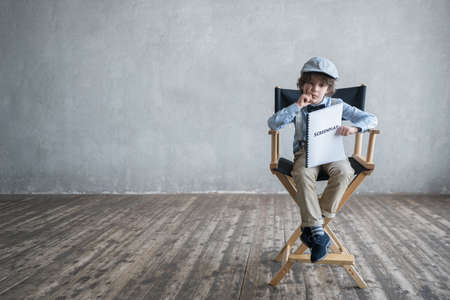 film director: Boy with a screenplay in studio Stock Photo
