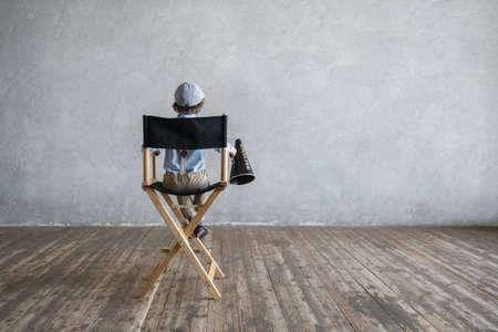監督の椅子の上に少年 写真素材