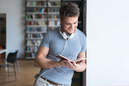 Young man reading a book in library Stockfoto