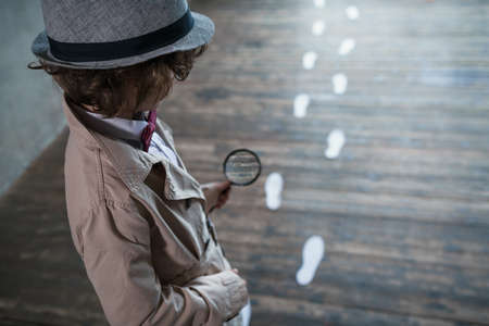 Detective with a magnifying glass Stock Photo