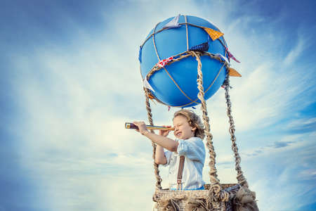Little boy with a spyglass on a balloon