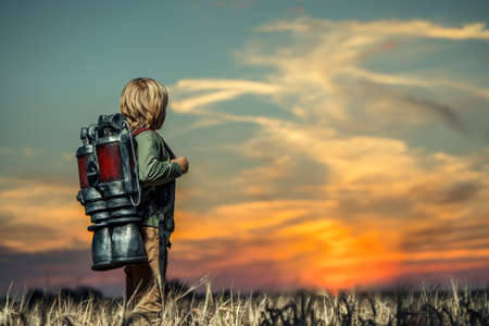 Boy with a technological backpack at sunset