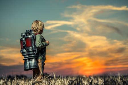 Jongen met een technologische rugzak bij zonsondergang