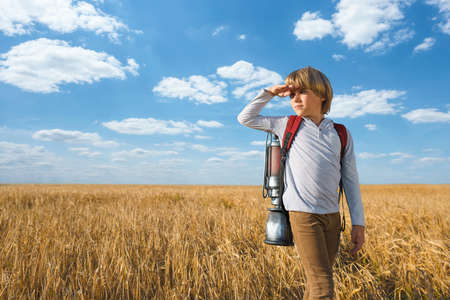 Boy with a technological backpack in a field