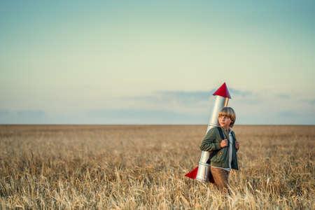 Niño con un cohete en un campo Foto de archivo - 72973517