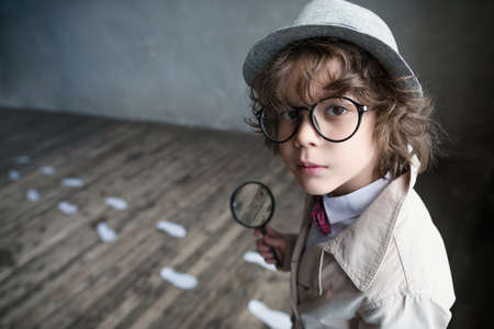 Little detective with a magnifying glass Stock Photo - 72973522