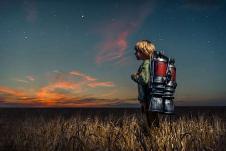 Little boy with a backpack at night