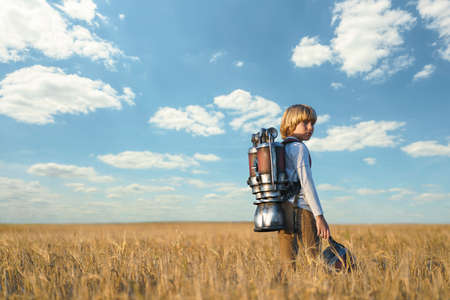 Little boy with a backpack in a field