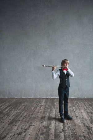 Little boy playing a flute