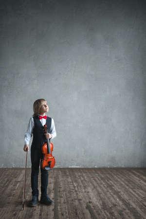 Kleine jongen met een viool binnenshuis Stockfoto