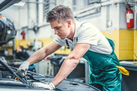 Jeune mécanicien au capot de voiture Banque d'images - 76226492