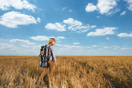 Little boy with a backpack in field