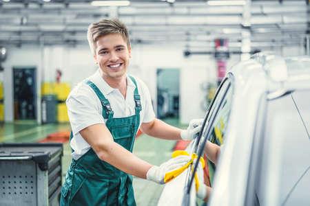 Smiling man washing car in service