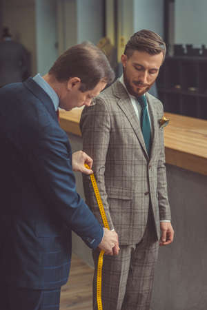 Tailor measures a man in studio