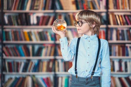 public aquarium: Boy with goldfish in library