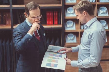 work book: Customer and tailor in studio Stock Photo