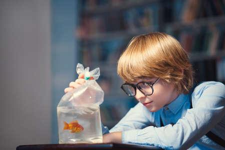 public aquarium: Little boy with a goldfish indoors