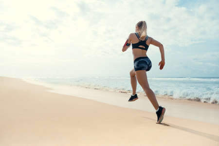 Running woman on the beach