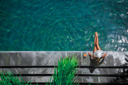 outerwear: Young woman by the pool Stock Photo