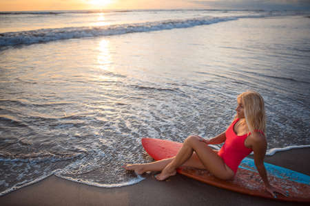 Beautiful young woman with surfboard