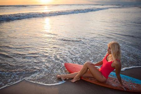 Schöne junge Frau mit Surfbrett Standard-Bild - 80118411
