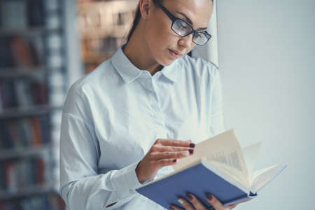 Jong meisje dat een boek leest Stockfoto