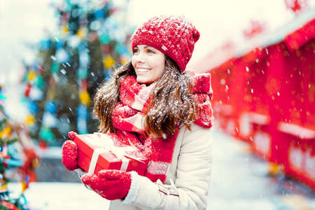 Young girl with a gift in winter 스톡 콘텐츠