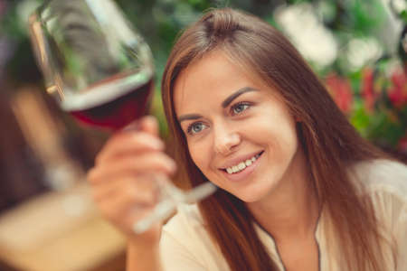 Smiling young girl tasting wine Stock Photo