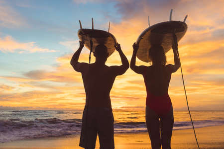 Young people with surfboard at sunset Imagens