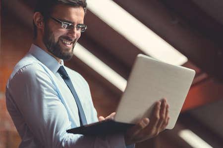 Happy businessman with laptop indoors Reklamní fotografie