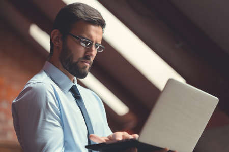 Businessman with laptop in the loft