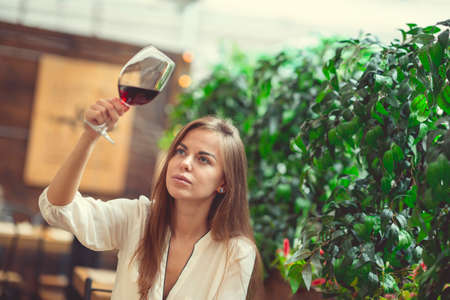 Young girl with a wine glass in a cafe