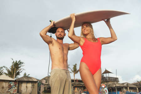 Happy couple with a surfboard