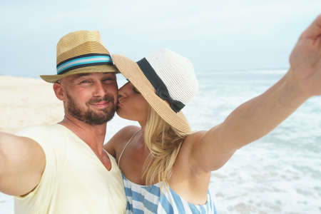 Kissing couple makes selfie outdoors